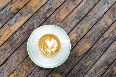 Cup of fresh creamy cappuccino with latte art on foam. Background of wooden table with shabby aged surface. Directly from above.