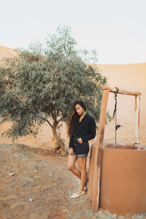 Fashion stylish portrait of young oriental woman in black clothes. Standing near well and tree in oasis in Sahara desert, Morocco.