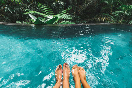 Couple feet together in luxury swimming pool with turquoise clear water outdoors with jungle view. Tropical Honeymoon, leisure vacations.