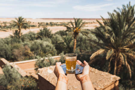 Woman hands with henna tattoo holding glass of traditional mint moroccan tea. Sand desert and palms on background.