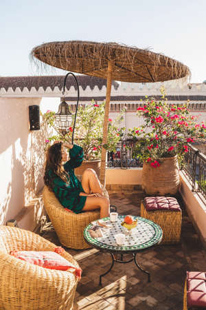 Woman enjoying breakfast on beautiful lounge hotel terrace in downtown of Marrakech at sunrise. Moroccan design with vintage elements - metal lantern, wicker chair, round table, and umbrella.
