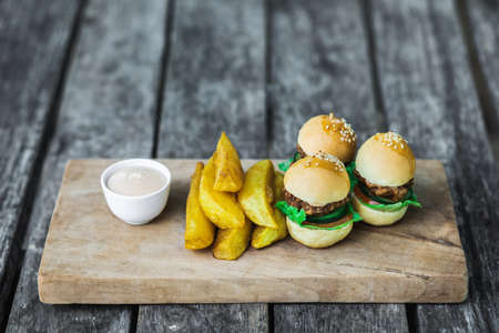 Three mini burgers with beef patty, french fries and mayonnaise on wooden board. Shabby aged table background. Unusual food serving. Fast food and unhealthy lifestyle.