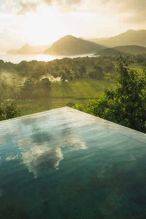 Infinity pool with amazing mountain and ocean view at sunset. Sun rays and mist. Cloud reflection in water. Luxury hotel viewpoint.