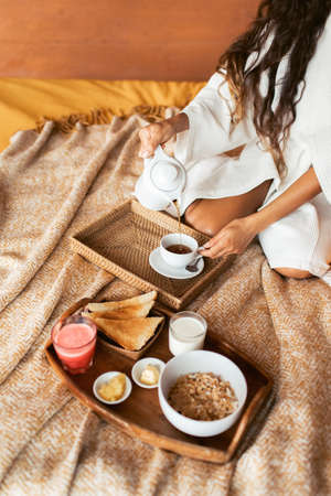 Healthy breakfast in bed with granola, crispy toast, butter, milk and watermelon juice. Woman pouring hot tea in cup on wooden tray.