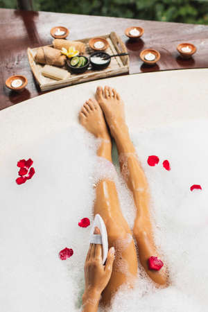 Woman washing legs in bath tub with foam bubbles and use natural loofah sponge. Spa treatment, body care, romantic mood.