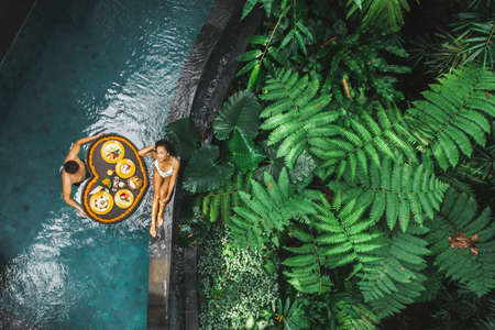 Travel happy couple in love eating floating breakfast in jungle swimming pool. Awakening in morning. Black rattan tray in heart shape, Valentines day or honeymoon surprise, view from above.