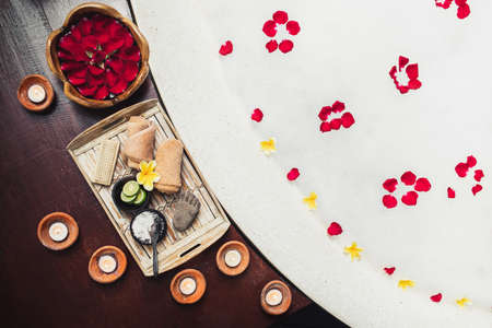 Romantic spa set with lime, scrub, salt, towels and brush in wooden tray. Flower petals in bath tub with foam and candles around. Organic and natural beauty treatment accessory. Standard-Bild