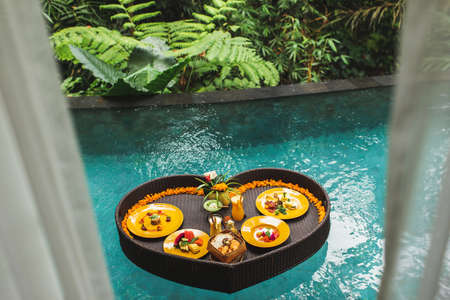 Floating breakfast in jungle swimming pool, tropical resort. Black rattan tray in heart shape, Valentines day or honeymoon surprise, view from above. Exotic summer diet. Tropical beach lifestyle. Standard-Bild