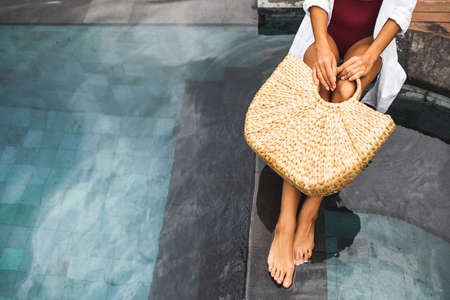 Woman near swimming pool holding in hands handmade straw wicker beach bag. Eco-friendly and zero waste tropical lifestyle. Organic and natural, plastic free.