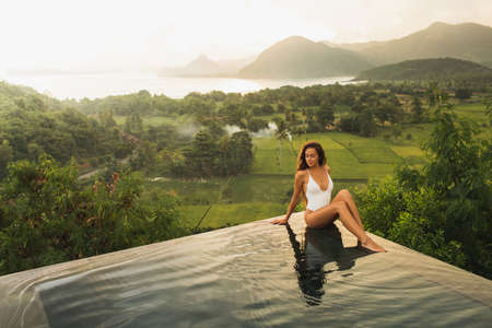 Dream journey in Asia. Woman sitting on edge luxury infinity pool an enjoying amazing mountain, rice terraces and coastline view at sunset. Inspiration travel destination.