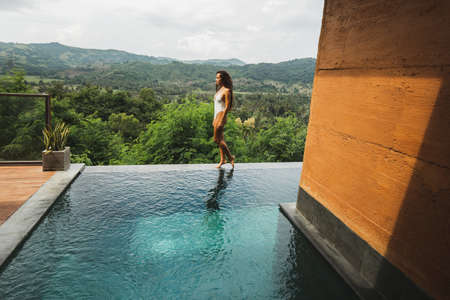 Slim beautiful woman in white swimsuit walking by edge of infinity swimming pool with amazing jungle and mountain view. Enjoying holidays in Asia.
