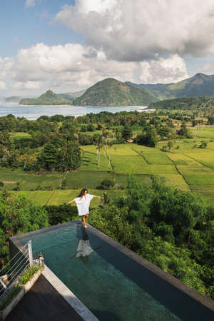 Woman in white tunic walking by the edge infinity pool with awesome view of rice terraces, mountains and ocean coast. Aerial view. Vacations in Asia.