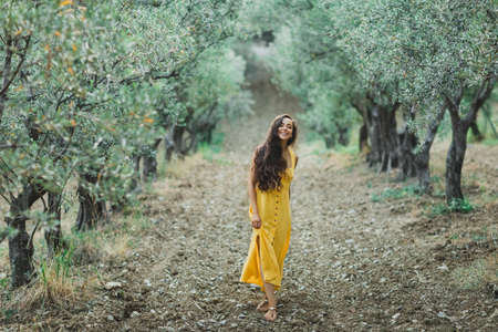 Young happy smiling woman walking in olive tree garden. Yellow linen summer dress. Trendy color and textile style.