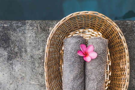Two gray hand towels in wicker basket on poolside in hotel spa. Pink frangipani flower as decoration. Beauty treatment.