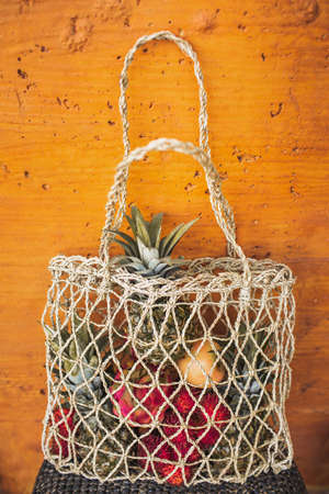 Mesh reusable shopping bag with fresh organic tropical fruit on orange wall background. Zero waste lifestyle. Raw food and vegetarian diet.
