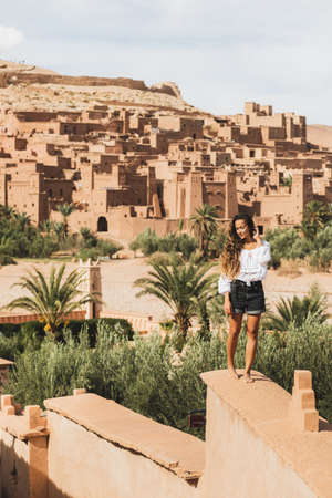 Beautiful young woman walking by fence of castle with view of Ait-Ben-Haddou kasbah on background. Travel in Morocco. Vertical photo. Standard-Bild