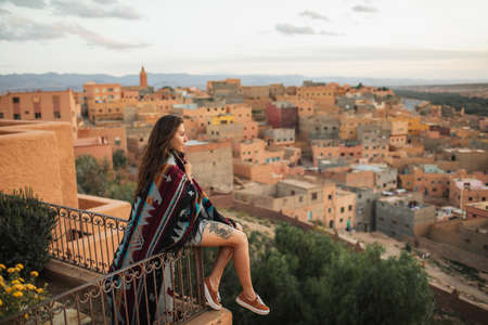 Woman sitting on roof terrace with aerial view of old arabian town Boumalne. Covered with traditional moroccan cape. Hippie style, tattoo on   leg. Standard-Bild