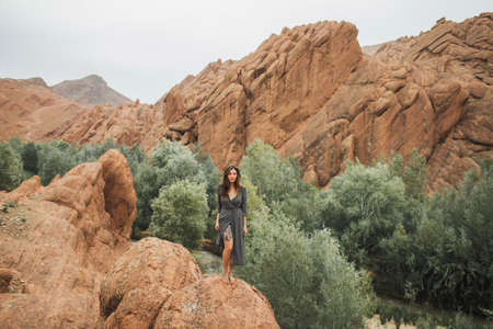 Portrait of beautiful european woman barefoot on background of Todra gorge canyon in Morocco. Long black dress and tattoo on naked leg. Standard-Bild