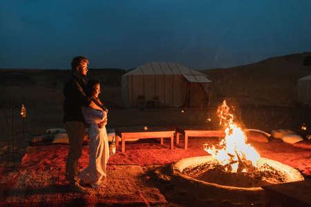 Couple hug in love near big campfire. Romantic night in glamping desert camp in Sahara, Morocco. Honeymoon.