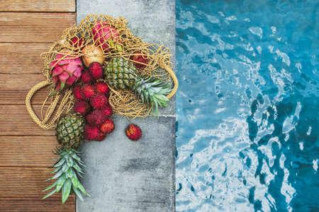 Flat lay of fresh tropical fruits pineapple, rambutan, dragon fruit in reusable mesh bag on pool edge. Zero waste lifestyle. Raw healthy food and vegetarian diet. Standard-Bild