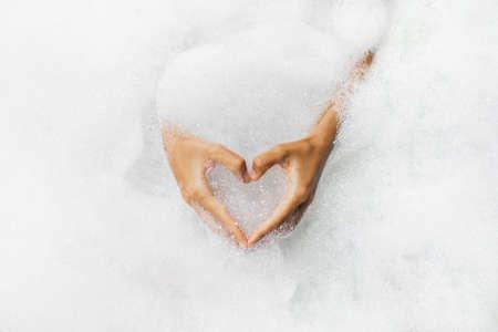 Woman hands in heart shape in bath full of foam bubbles close-up. Spa beauty treatment. Love symbol