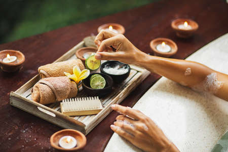 Beauty spa treatment concept. Woman hands hold lime from natural cosmetics set on wooden tray. Romantic mood, candles around.