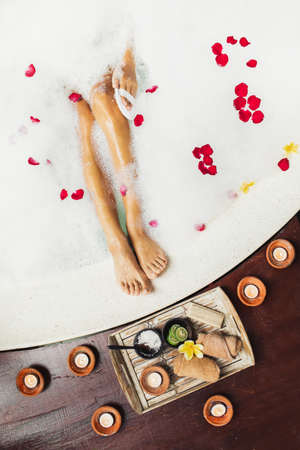 Woman legs in bath tub with foam bubbles and candles around. Romantic spa set with lime, scrub, salt, towels and brush in wooden tray. Organic and natural beauty treatment.
