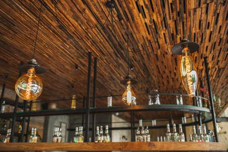 Creativity designed different shapes electric bulb lamps in restaurant interior decor. Cafe bar blurred background. Standard-Bild