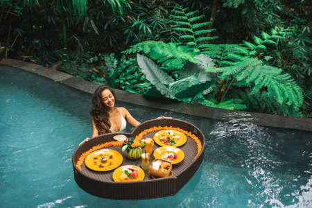 Woman relaxing and having floating breakfast in jungle pool on luxury villa in Bali. Valentines day or honeymoon surprise. Tropical travel lifestyle. Black rattan tray in heart shape.