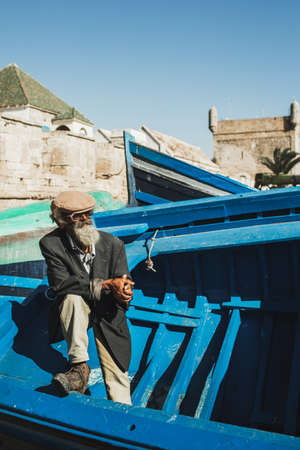 ESSAOUIRA, MOROCCO - SEPTEMBER 10, 2019: Old senior fisherman on blue wooden boat in Essaouira harbor. Stylish look, hat, beard, sunglasses and jacket. Moroccan people.