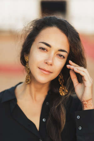 Close up portrait of young oriental brunette woman with long curly hair. Black shirt and golden earrings. Pretty female face.
