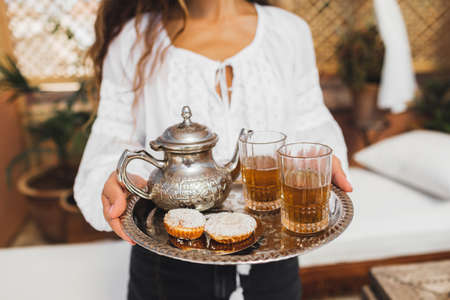 Woman hands holding silver tray with traditional moroccan mint tea, cookies and vintage teapot. Hospitality and service in Morocco. Standard-Bild