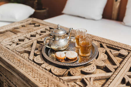Traditional moroccan mint tea with cookies on silver tray on carved wooden table. Beautiful vintage style, hospitality in Morocco.