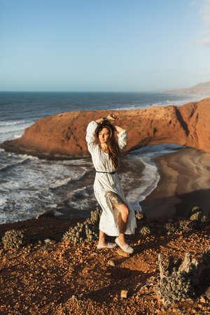 Portrait of young stylish beautiful woman in white dress on background of Legzira beach in Morocco. Tattoo on naked leg. Standard-Bild