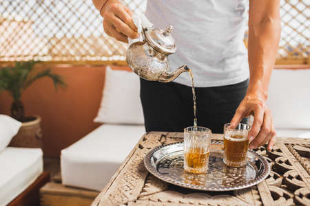 Man holding in hand silver vintage teapot and pouring traditional mint sweet moroccan tea. Arabian hospitality and service. Standard-Bild