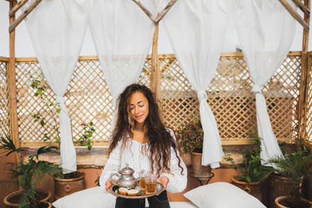 Beautiful young oriental woman holding tray with traditional moroccan mint tea, cookies and silver teapot. Hospitality in Morocco. Standard-Bild