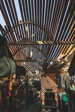 Selling of different goods in souk medina Marrakesh. Amazing day sun light and shadows. Moroccan traditional local market. Standard-Bild