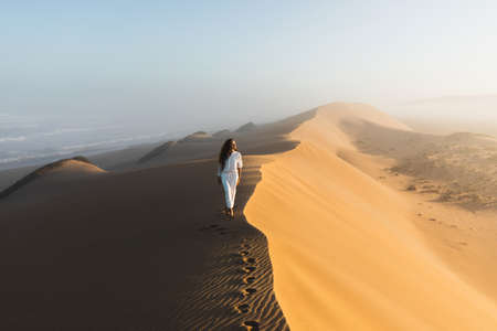 Woman in white clothes walking by top of huge sand dune near ocean coast in Morocco. Beautiful warm sun light and mist in morning. Sahara desert.