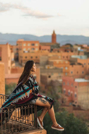 Woman sitting on roof terrace with aerial view of old arabian town Boumalne. Covered with traditional moroccan cape. Hippie style, tattoo on leg.