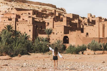 Woman enjoying popular landmark ksar Ait-Ben-Haddou. View from behind. Travel in Morocco, Ouarzazate. Wanderlust concept.