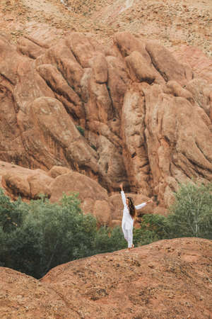 White woman walking on background of Todra gorge canyon landscape in Morocco. Red color mountains formed by weathering. Travel in Africa. Harmony with nature.