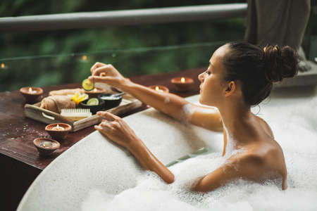 Woman taking a bath. Tub with foam bubbles. Romantic spa treatment, body care. Natural cosmetics set on wooden tray.