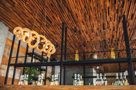 Creativity designed electric bulb lamp wrapped with rope. Eco-friendly style without plastic. Cafe bar blurred background. Standard-Bild