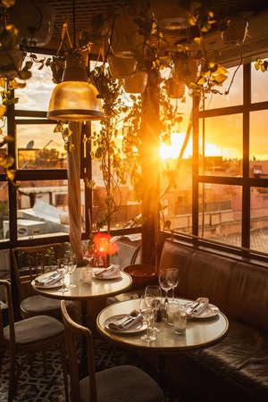 Table in restaurant served for romantic dinner on rooftop terrace in sunset light. Love in the air. Standard-Bild