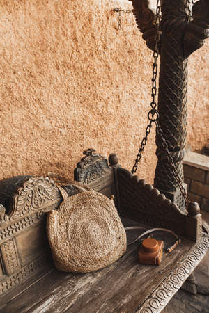 Beautiful wooden carved swing on chains. Handmade wicker straw bag and leather case for vintage photo camera. Terracotta wall.