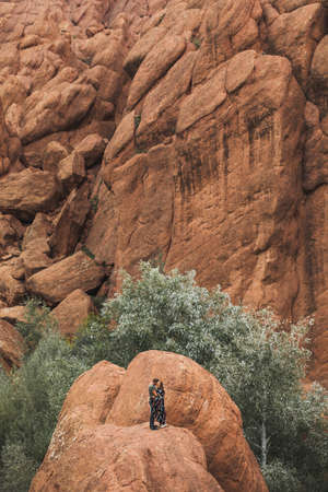 Couple in love on background of Todra gorge canyon landscape in Morocco. Red color mountains formed by weathering. Travel in Africa. Standard-Bild