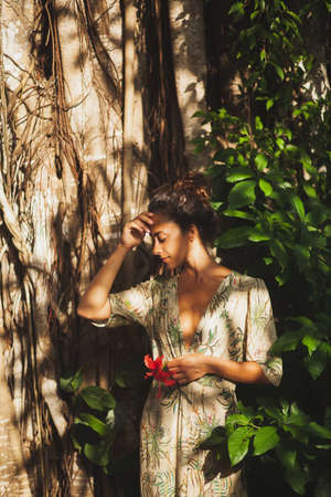 Portrait of pretty asian woman in green dress in tropical garden. Beautiful sunset light, huge tree, amazing nature.