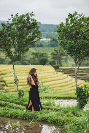 Woman walking against amazing Jatiluwih rice terraces in Bali. Beauty and harmony in nature. Wearing in long black dress.