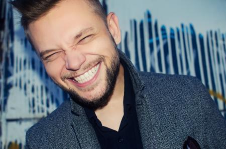 homme riant positif avec un sourire dent blanche sur le fond d'un mur peint Banque d'images