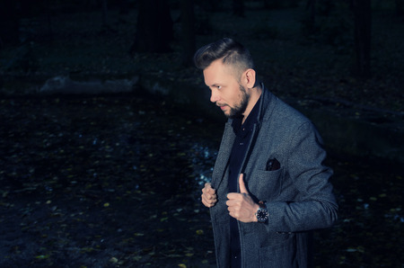 lapels: stern bearded man in an aggressive pose with his hands on lapels of his jacket in the park at night Stock Photo